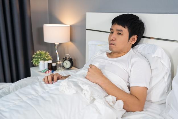 Homem doente é dor de cabeça e usando o termômetro para verificar sua temperatura na cama