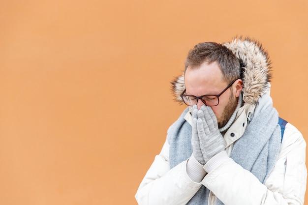 Homem doente em uma parca branca espirrando, sofrendo de nariz entupido, ao ar livre, parede laranja na superfície, copie o espaço. resfriado comum, conceito de temporada de gripe.