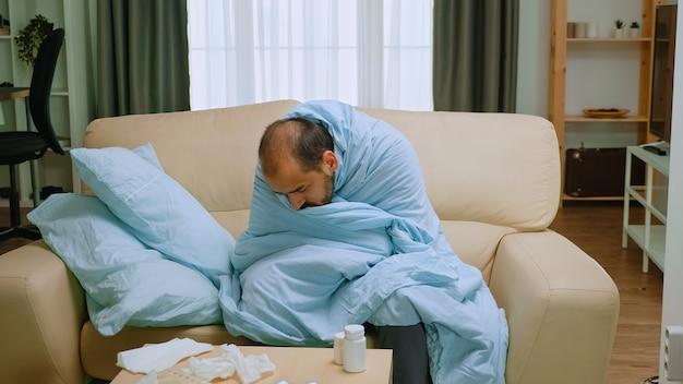 Homem doente embrulhado em cobertor durante um surto cobiçoso.
