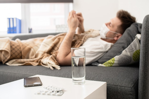 Homem doente encontra-se debaixo de um cobertor com um tablet. perto de um copo de água e comprimidos