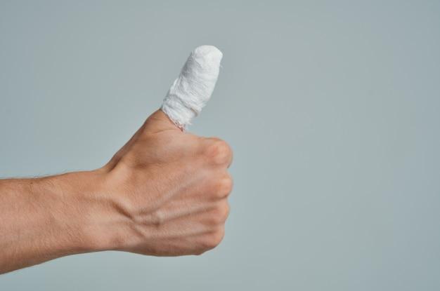 Homem doente enfaixou a mão com curativo nos dedos, medicamento hospitalar
