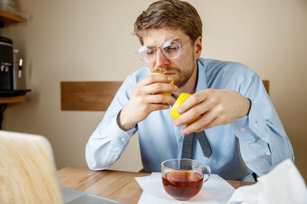 Homem doente enquanto trabalhava no escritório, empresário pegou resfriado, gripe sazonal.