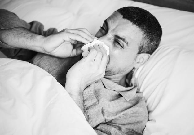 Homem doente espirrando na cama