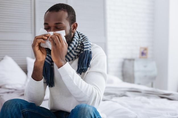 Homem doente. homem calmo e doente assoando o nariz enquanto está sentado na beira de uma cama em seu quarto confortável