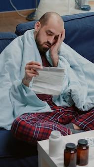 Homem doente lendo folheto informativo de medicamentos