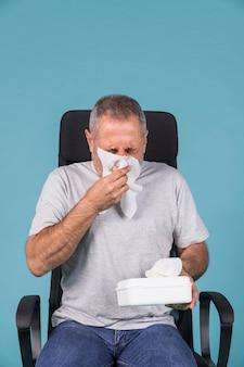 Homem doente maduro assoar o nariz com tecido