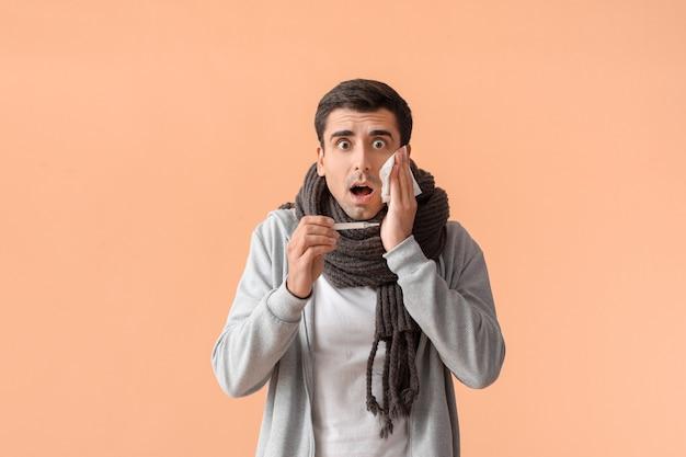 Homem doente medindo temperatura na superfície colorida