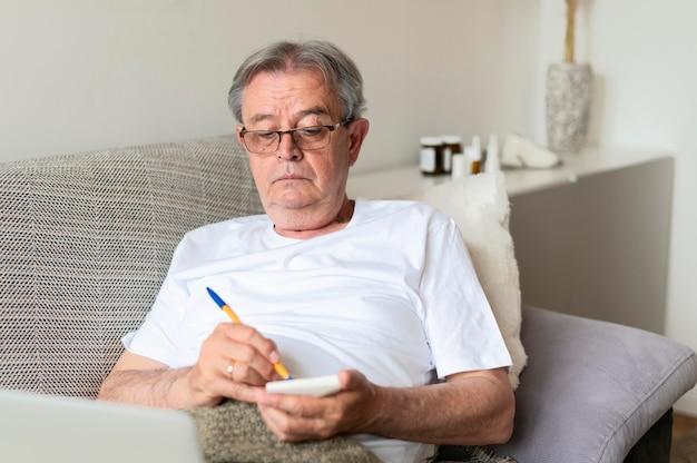 Homem doente médio baleado no sofá com notebook