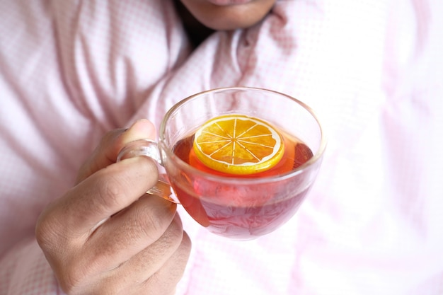 Homem doente não reconhecido bebendo chá de limão close-up.