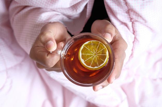 Homem doente não reconhecido bebendo chá de limão de perto