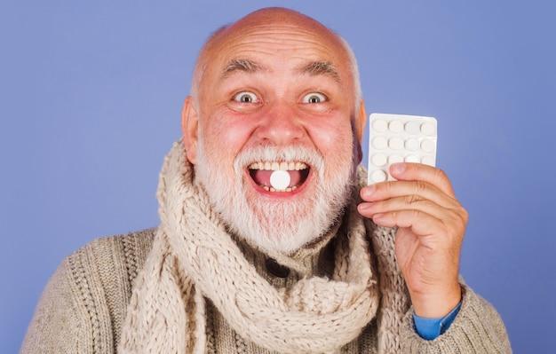 Homem doente no lenço com pílulas de dor de garganta. pílula de tratamento. homem sênior tomando pílulas farmacêuticas