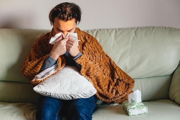 Homem doente segura tecido ao redor do nariz