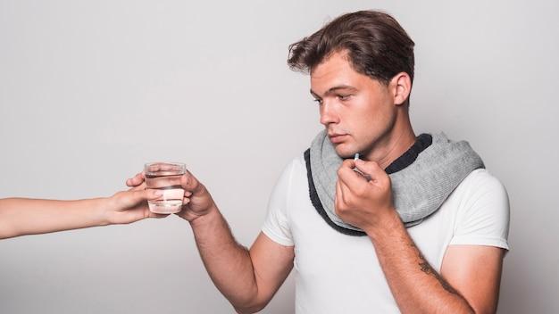 Homem doente, segurando, cápsula, levando, vidro água, de, pessoa, mão