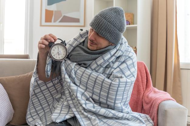 Homem doente sem noção com lenço no pescoço e chapéu de inverno embrulhado em xadrez segurando e olhando para o despertador sentado no sofá na sala de estar