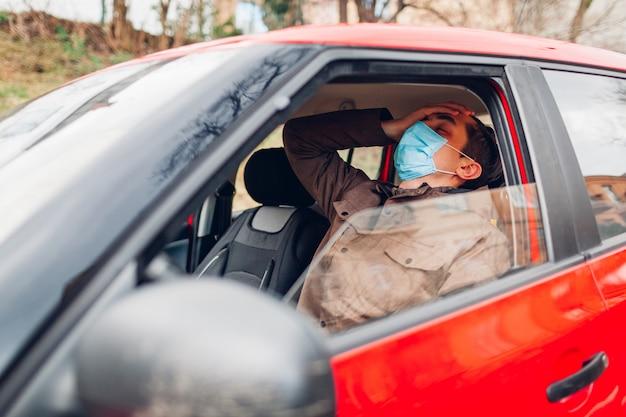 Homem doente sentado no carro usando máscara protetora sente febre doente tem gripe covid-19 coronavírus.