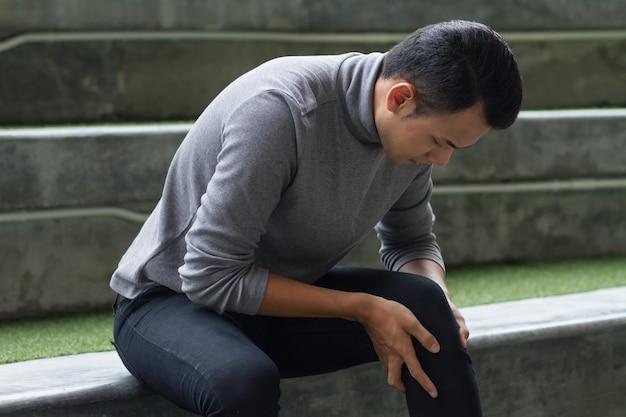 Homem doente sofre de dores nas articulações do joelho, osteoartrite
