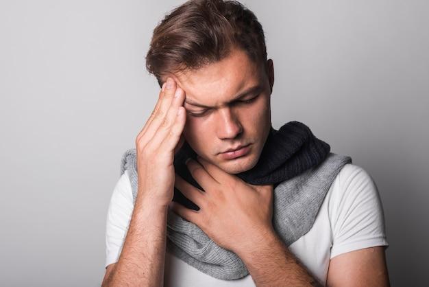 Homem doente, sofrendo de dor de cabeça e frio contra fundo cinza