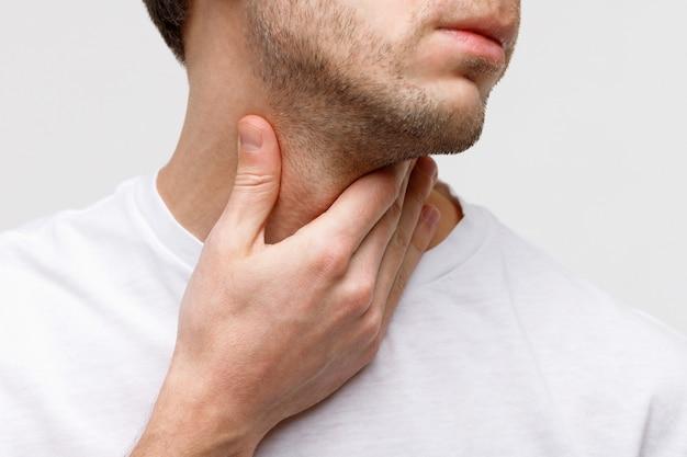 Homem doente, sofrendo de problemas na garganta, glândula tireóide