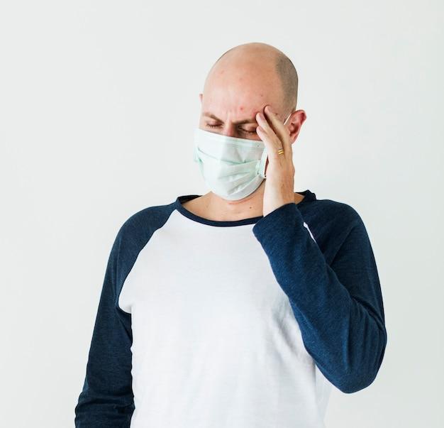 Homem doente usando máscara cirúrgica tendo uma dor de cabeça