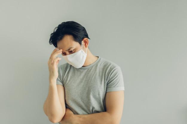 Homem doente usando máscara higiênica branca em camiseta cinza