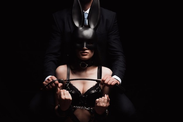 Homem dominante com um chicote flogger e uma garota submissa de cueca, máscara e algemas