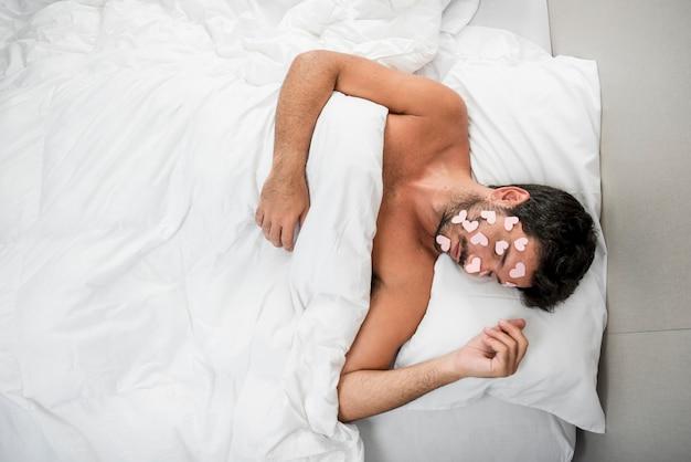 Homem dormindo com corações de papel no rosto
