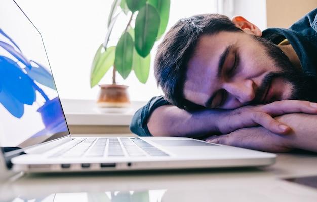 Homem dormindo com seu laptop