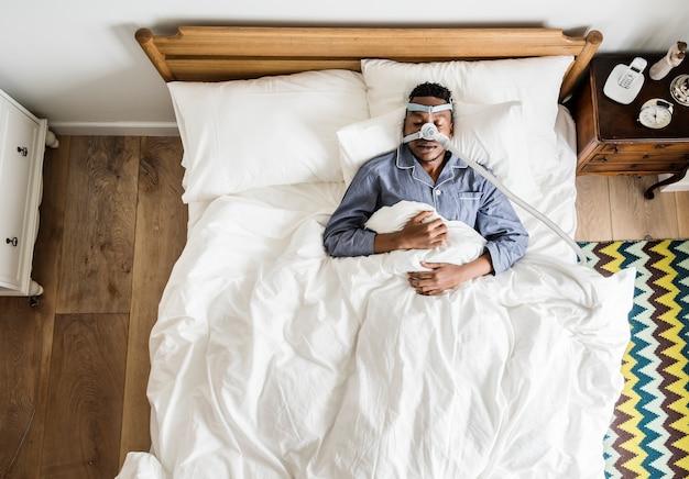 Homem dormindo com uma máscara anti-ronco