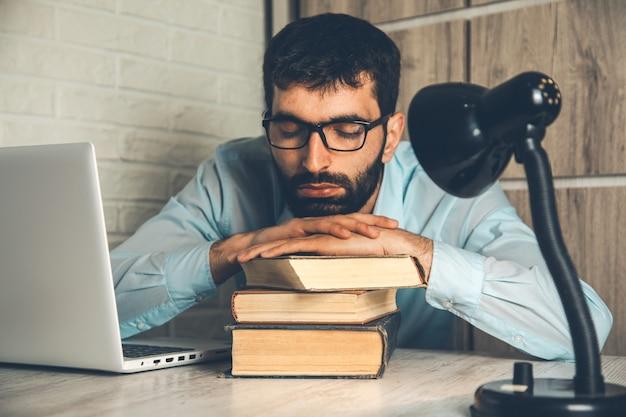 Homem dormindo no livro com o computador na mesa