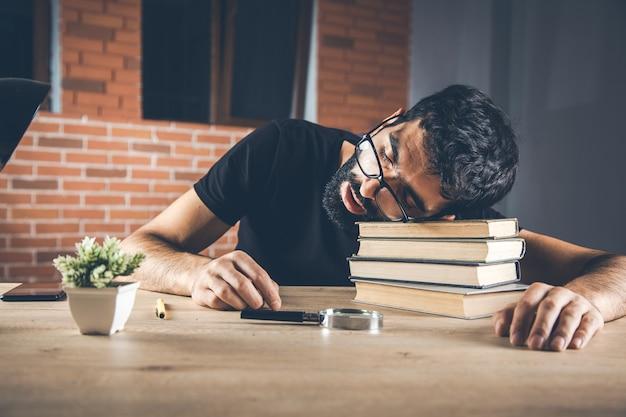 Homem dormindo no livro no escritório