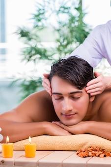 Homem durante a sessão de massagem no salão spa