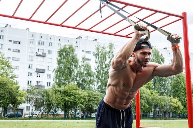 Homem durante treino com correias de suspensão