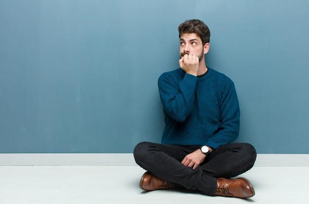 Homem duvidando ou pensando, mordendo o lábio e se sentindo inseguro e nervoso, olhando para copiar o espaço ao lado