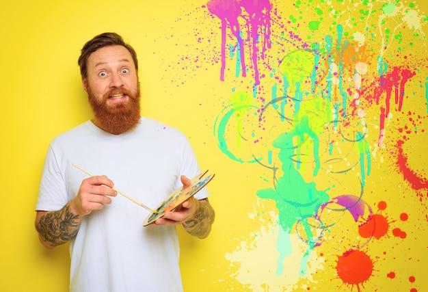 Homem duvidoso com barba e tatuagem está pronto para desenhar com pincéis