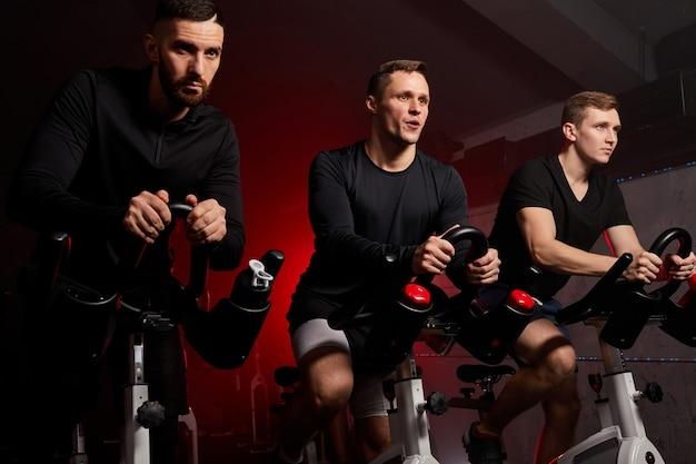 Homem e amigos em bicicleta fitness na academia durante o treino, eles estão ansiosos, homens fortes e musculosos em roupas esportivas