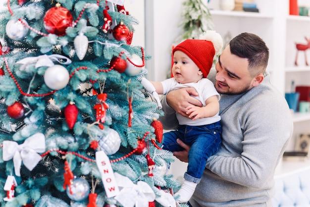 Homem e bebê fofo estão prontos para comemorar o ano novo. feliz pai brinca com seu filho bebê perto de árvore de natal na noite de natal.