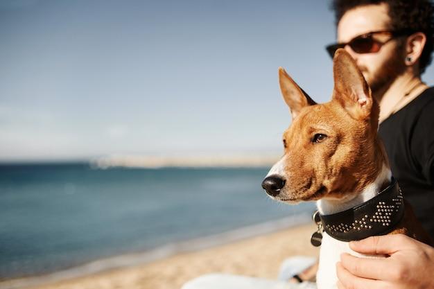 Homem e cachorro na praia admirando o mar