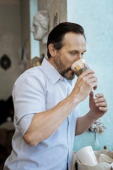 Homem e café. homem bonito de cabelos escuros tomando café perto da janela se preparando para o trabalho