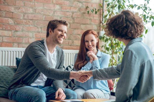Homem e corretor apertando as mãos no escritório