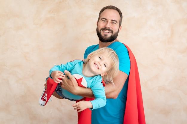 Homem e criança super-herói em casa. pai e filho super-herói se divertindo juntos.