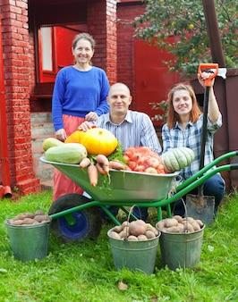 Homem e duas mulheres com vegetais colhidos