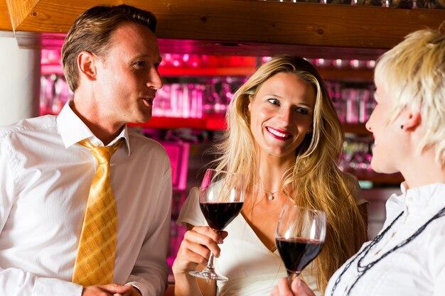 Homem e duas mulheres no bar do hotel