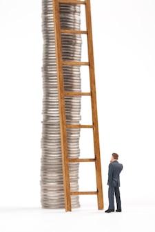 Homem e escada com pilhas de moedas no fundo branco