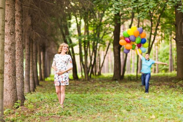 Homem e esposa grávida com balões ao ar livre