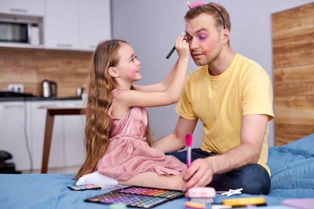 Homem e filha estão brincando em casa, sentados na cama.