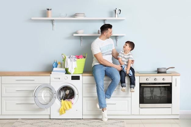 Homem e filho pequeno lavando roupa em casa