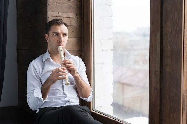 Homem e flauta ao lado de janelas