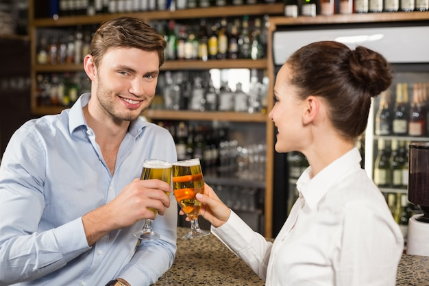 Homem e garçonete brindando com cervejas