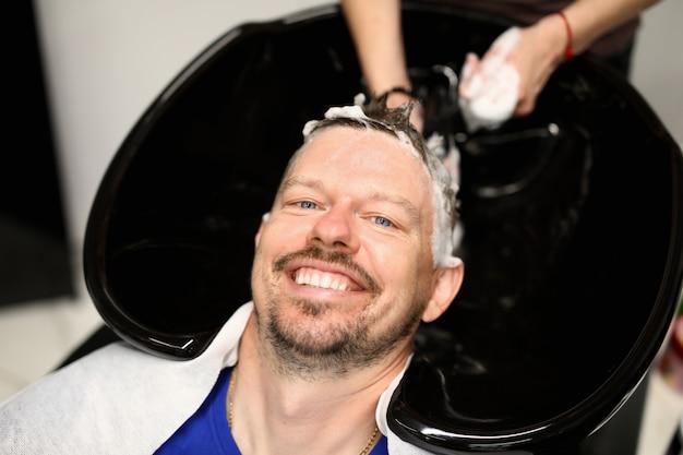 Homem é lavado o cabelo no salão de beleza após o corte de cabelo.