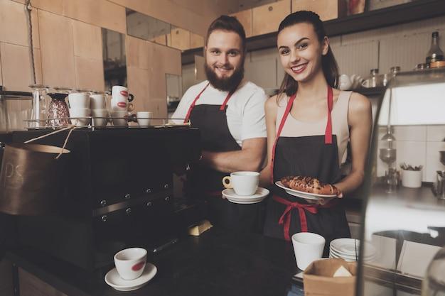 Homem e linda garota barista atrás do balcão